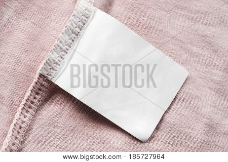 Blank white clothes label on pink cloth as a background