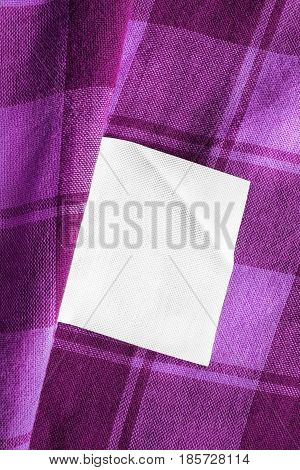 White blank clothes label on purple plaid cotton as a background