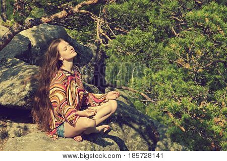 Young beautiful woman meditating at the mountains. relaxation outdoors. nature freedom and inspiration