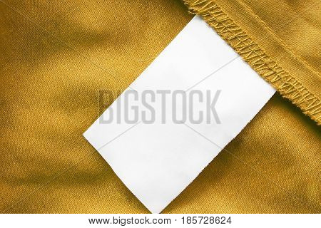 Blank white clothes label on yellow linen as a background