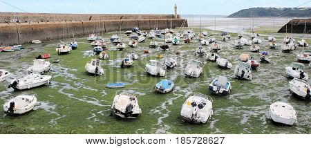 Boats laying in harbour by low tide