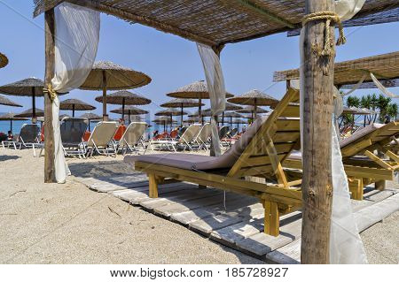 Beautiful Ionian sandy resort beach in Greece with sunbeds and sunshades. Vacation destination. Public beach