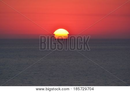 Red sky and dark blue sea the setting sun a half under the horizon and reflection on the sea surface