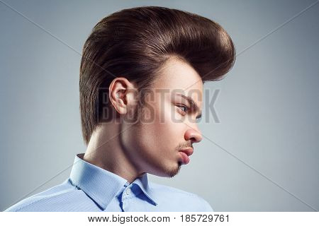 Side view of young man with retro classic pompadour hairstyle. studio shot.