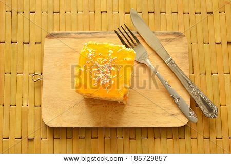orange butter cake topping colorful candy with fork and knife on wooden chop block