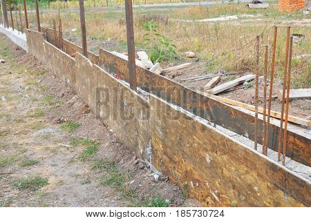 Close up on Building concrete slab foundation for new fence. Construction site during concrete pouring works with form work.