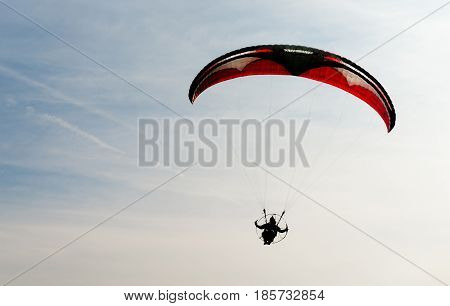 Person holds two directional controls flying with a propeller and motor below a cloth parachute