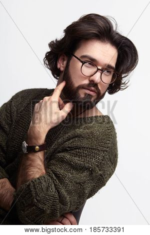 Vertical studio portrait of a confident man wearing sweater and glasses touching beard and looking away.