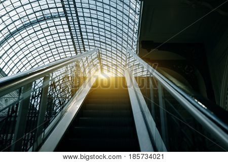 Escalator Moving Up At Indoors In Building With Transparent Roof