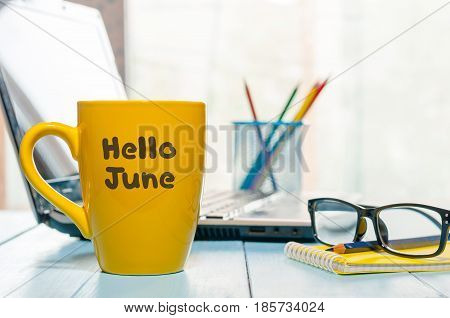 Hello June - inscription at yellow morning coffee or tea cup at business office background. First summer day, Calendar concept.