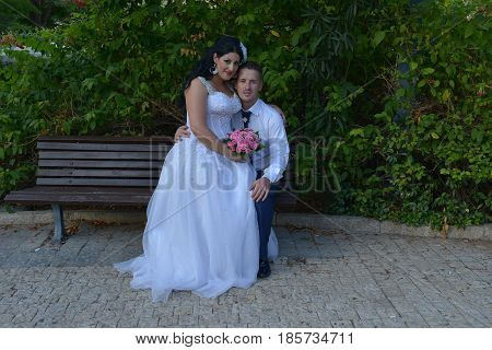 Young bride and groom posing for the camera outdoors