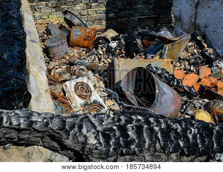 The stove is to blame for the fire among the charred logs metal objects mutilated by fire.