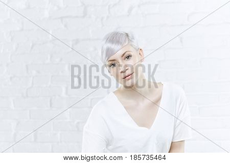 Closeup portrait of young woman with short platinum blonde hair.