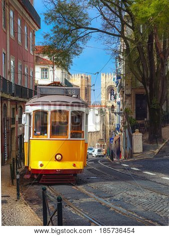 Famous vintage yellow 28 tram on street of Alfama, the oldest district of the Old Town, Lisbon, Portugal