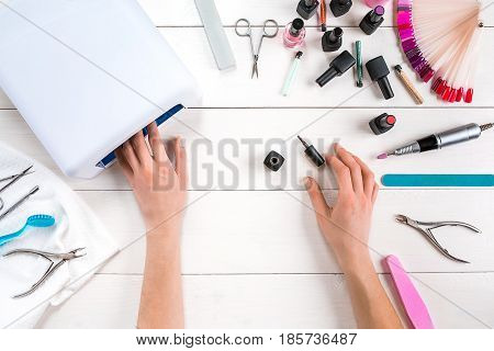 Nail care. Manicure set and nail polish on wooden background. Top view. Manicurist. Manicure for yourself