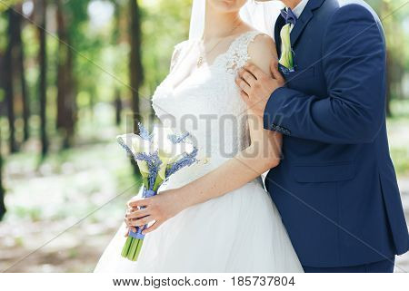 the groom in a beautiful blue suit hugging the bride with a bouquet of Calla lilies in hand