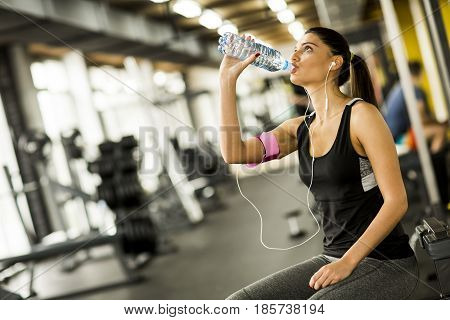Attractive Sport Young Woman Drinking Water While Sitting And Resting After Workout