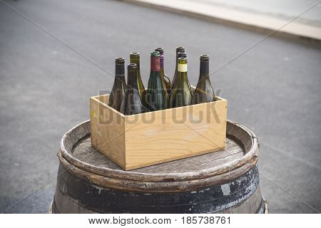 wooden box with empty wine bottles on an old barrel