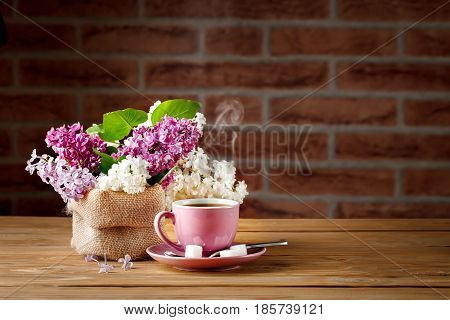 Still life with colorful branches of lilac and a Cup of coffee on a wooden table.
