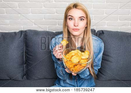 Portrait Of Smiling Girl Eating Chips At Home On Sofa