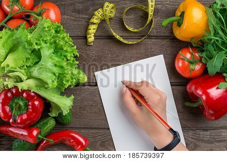 Sport and diet. Vegetables and centimeter. Peppers, tomatoes, salad on rustic background. Top view. Copy space