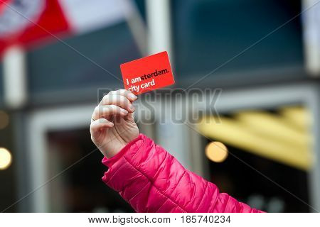 Amsterdam, Netherlands - April, 2017: I am Amsterdam city discount card on woman hand in Amsterdam, Netherlands