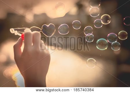 woman blowing bubble. Heart-shaped bubble. Bubbles in the air