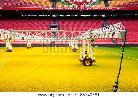 Amsterdam, Netherlands - April, 2017: Interior view of Amsterdam Ajax Football Arena. System of care and sprinkling of the lawn grass at the stadium