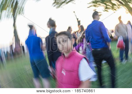 Kid standing in crowd of people (Note: Motion blur is real and not made in postproduction)