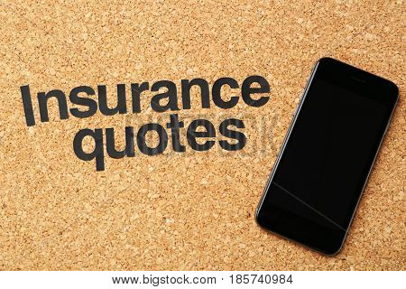 Text INSURANCE QUOTES and smartphone on cork background