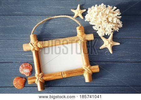 Travel concept. Bamboo frame with space for text, starfishes and shells on wooden background