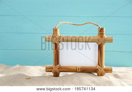 Bamboo frame with space for text on sand against color background