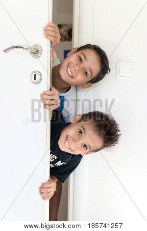 Children peeking out of the open room door