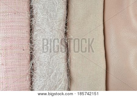 Twisted cane cotton woolen and leather fabrics of same nude or pink color folded side by side