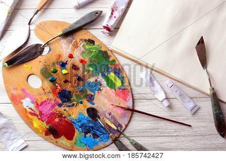 Composition with palette, oil paints and painting tools on table