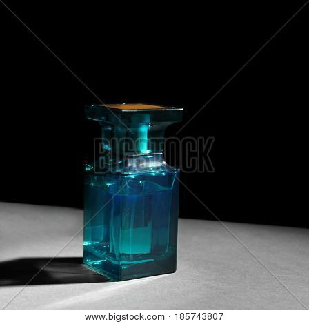 Bottle of modern male perfume on dark background