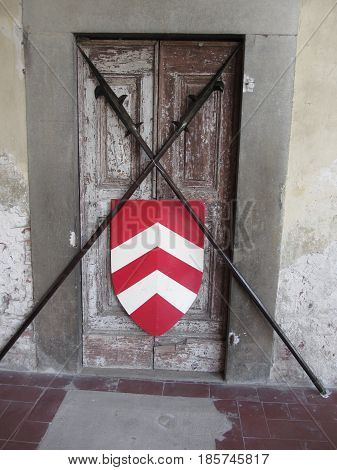 Barred door with medieval crossed spears and shield . Entry blocked . Access denied . Photo taken during outdoor public event (no ticket required) in public place . Pistoia Italy