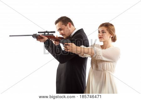 A couple holding guns and wearing fancy clothes