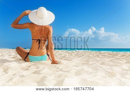 Tanned young girl sitting on the beach wearing blue striped swimwear and big hat.