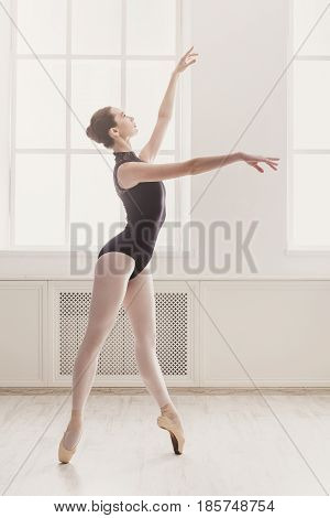 Graceful ballerina in black practice ballet positions near large window in light hall. Ballet class training, high-key soft toning. Vertical image