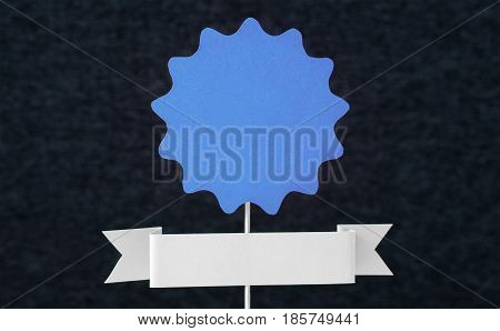 Blue paper sign on wooden stick with dark background. Certificate, badge, seal or banner template cut from cardboard for designers. Blank empty copy space for text. Authentic handmade handcraft.