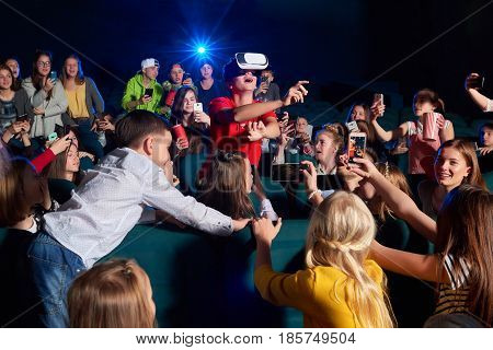 Young boy looking amazed and surprised pointing away with his finger wearing virtual reality glasses at the movie theatre his classmates looking at him copyspace film projector light beam technology.