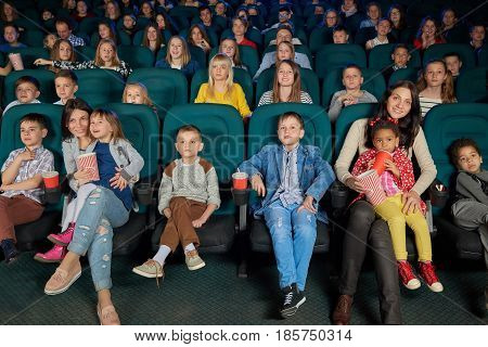 Shot of a cinema hall full of little children enjoying watching a movie during holidays kids childhood carefree relax entertainment weekend activity preschool fun emotions positivity concept.
