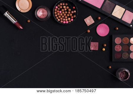 Makeup cosmetics frame on black background. Top view, flat lay with copy space. Beauty tools palettes collection, lipstick, eyeshadow, ball blush, foundation and more