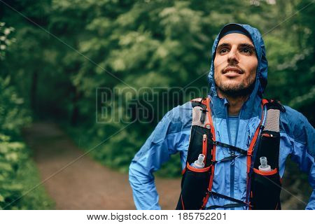Competitive, athletic young man pauses before running off road outdoors through the woods on a trail in the afternoon wearing sportswear.