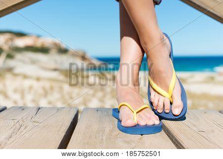 Woman Wearing Flip-Flops While Standing On Board Walk