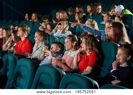 Young girls enjoying watching a movie together at the cinema laughing pointing at the screen with their fingers copyspace carefree positive emotions expressing vitality lifestyle leisure entertaining.