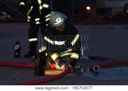Hamburg, Germany - April 18, 2013: Hdr - Firefighter In Action With A Fire Hose In The Evening