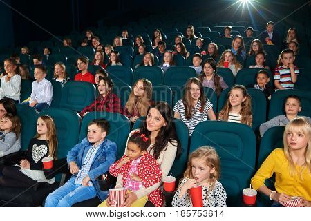 Cinema hall full of children and their parents enjoying movie premiere together entertainment activity hobby lifestyle people emotions excitement amusement expressive concept.