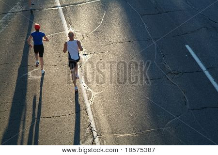 A pair of marathon runners head towards the rising sun during the opening stages of a race.